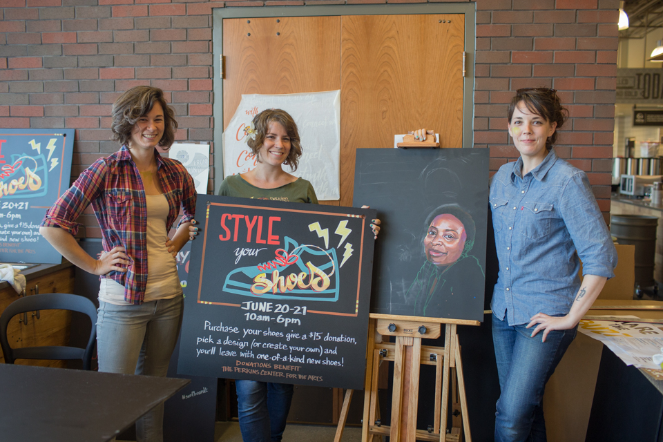 From left: graphic artists Kelly Franklin, Monica Kelly, and Carol Paist display some of the hand-lettered signs they've created in the market's in-house art department. Credit: Tricia Burrough/Lilac Blossom Photography.