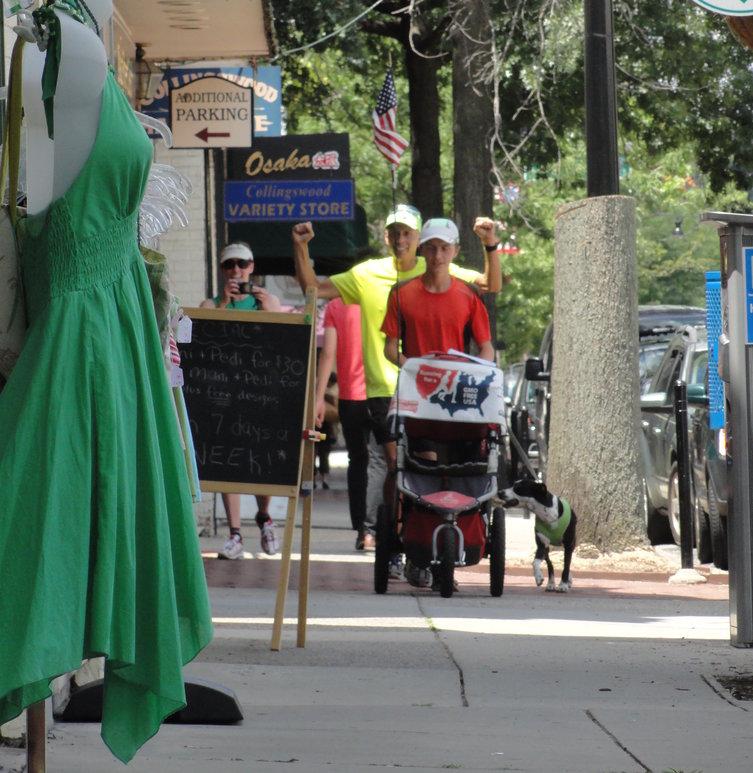 Brett Wilcox (in yellow) and his son David push their jogging stroller through Collingswood. Credit: Matt Skoufalos.