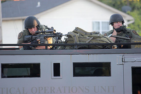 Snipers from the St. Louis County police train their arms on crowds of protesters in Ferguson, MO. Credit: Danny Wicentowski / Riverfront Times.
