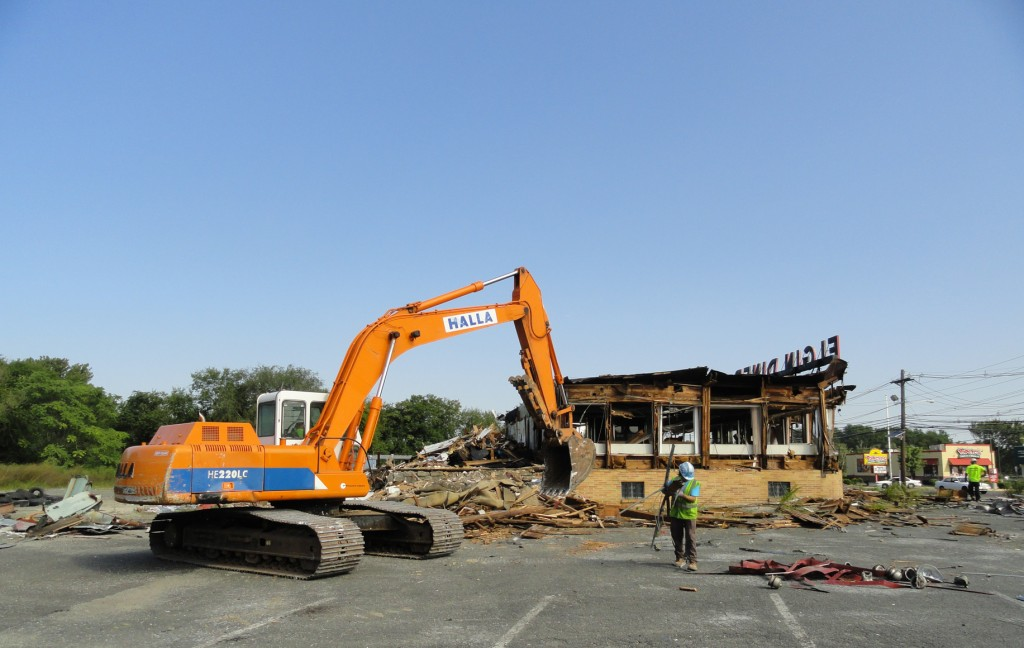 A backhoe sifts through pieces of the antique Elgin Diner in Camden City. Credit: Matt Skoufalos.