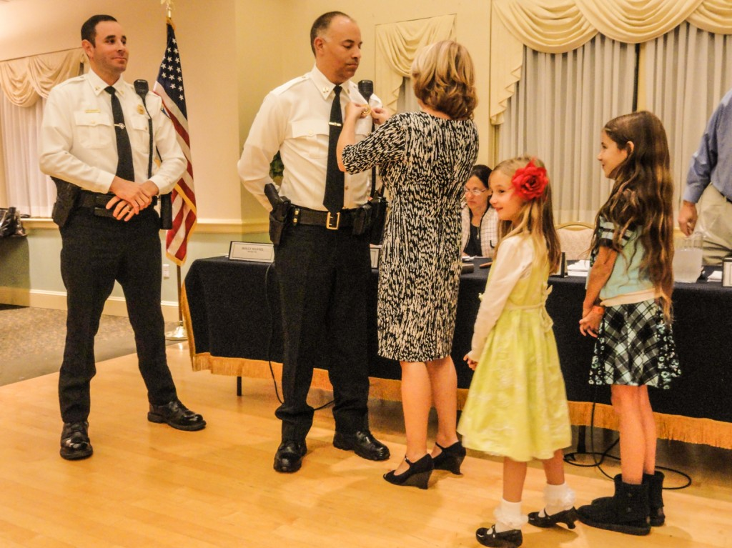 Frank Lee receives his captain's badge from his wife, Sarah, as their daughters look on. Credit: Matt Skoufalos.