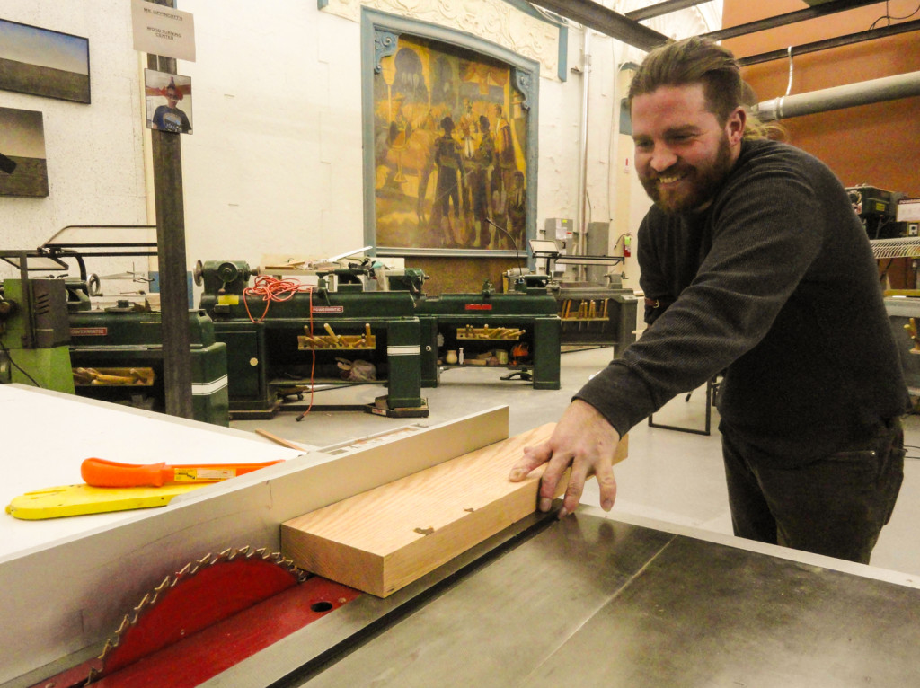 Faulseit demonstrates his new arm in the woodshop. Credit: Matt Skoufalos.