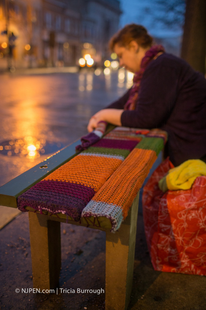 Elspeth Abel Slater affixes her yarnbomb to a bench in Collingswood. Credit: Tricia Burrough.