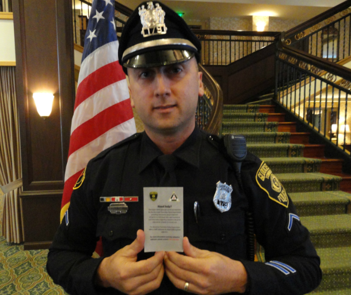 Gloucester Township Ptl. Ernie Basile displays a Project SAVE card. Credit: Matt Skoufalos.
