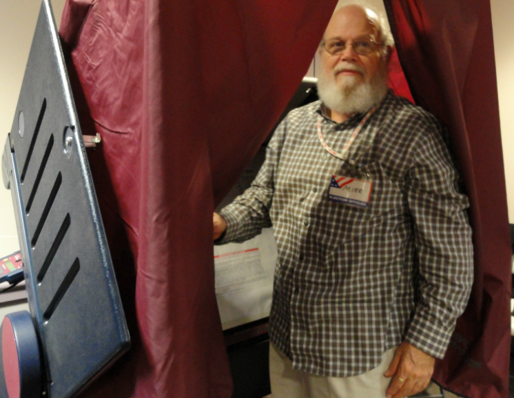 Poll worker Mike Burgoon demonstrates the booth. Credit: Matt Skoufalos.