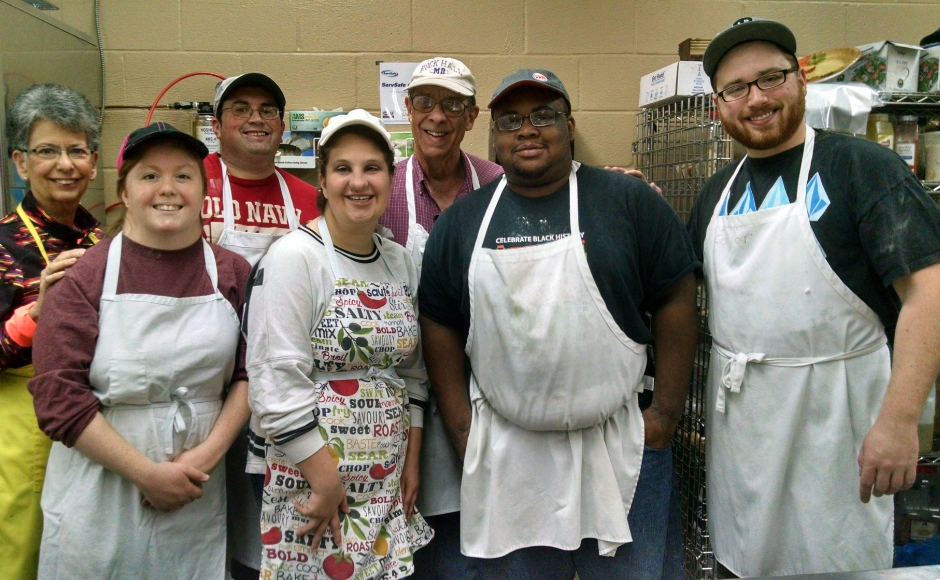 Members of the Soups and Sweets class pose for a group shot in their kitchen. Credit: Matt Skoufalos.