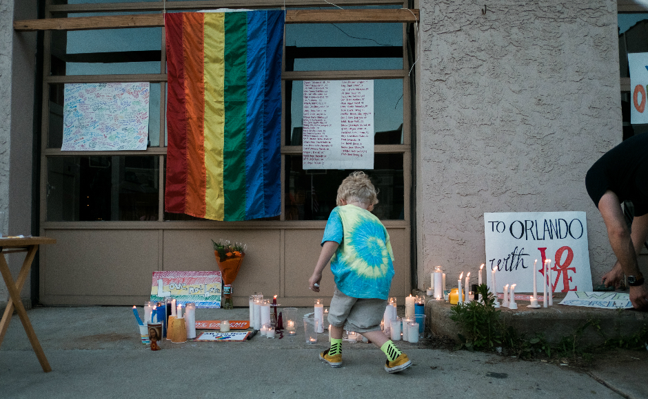 A child lights a candle at a vigil for victims of the Orlando nightclub shooting in Collingswood. Credit: Tricia Burrough.