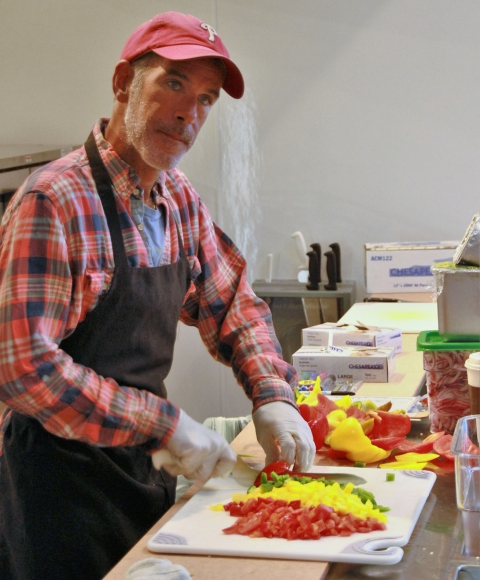 Bill Videtto of Drexel Hill chops peppers at the Naked Lunch counter at MOM's Organic Market Cherry Hill. Credit: Rob Smith.